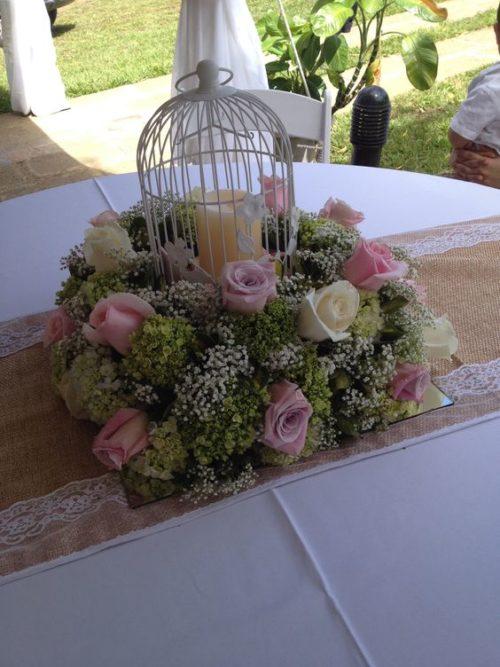 centro de mesa en forma de globo aerostatico hecho con globo canastita de mimbre y ramo de flores