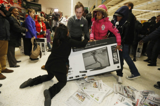 "28 Nov 2014, London, England, UK --- Shoppers wrestle over a television as they compete to purchase retail items on ""Black Friday"" at an Asda superstore in Wembley, north London November 28, 2014. Britain's high streets, malls and online sites were awash with discounts on Friday as more retailers than ever embraced U.S.-style ""Black Friday"" promotions, seeking to kickstart trading in the key Christmas period. In the United States the Friday following the Thanksgiving Day holiday is called Black Friday because spending usually surges and indicates the point at which American retailers begin to turn a profit for the year, or go ""into the black"". REUTERS/Luke MacGregor (BRITAIN - Tags: BUSINESS ANNIVERSARY TPX IMAGES OF THE DAY) --- Image by © LUKE MACGREGOR/Reuters/Corbis"